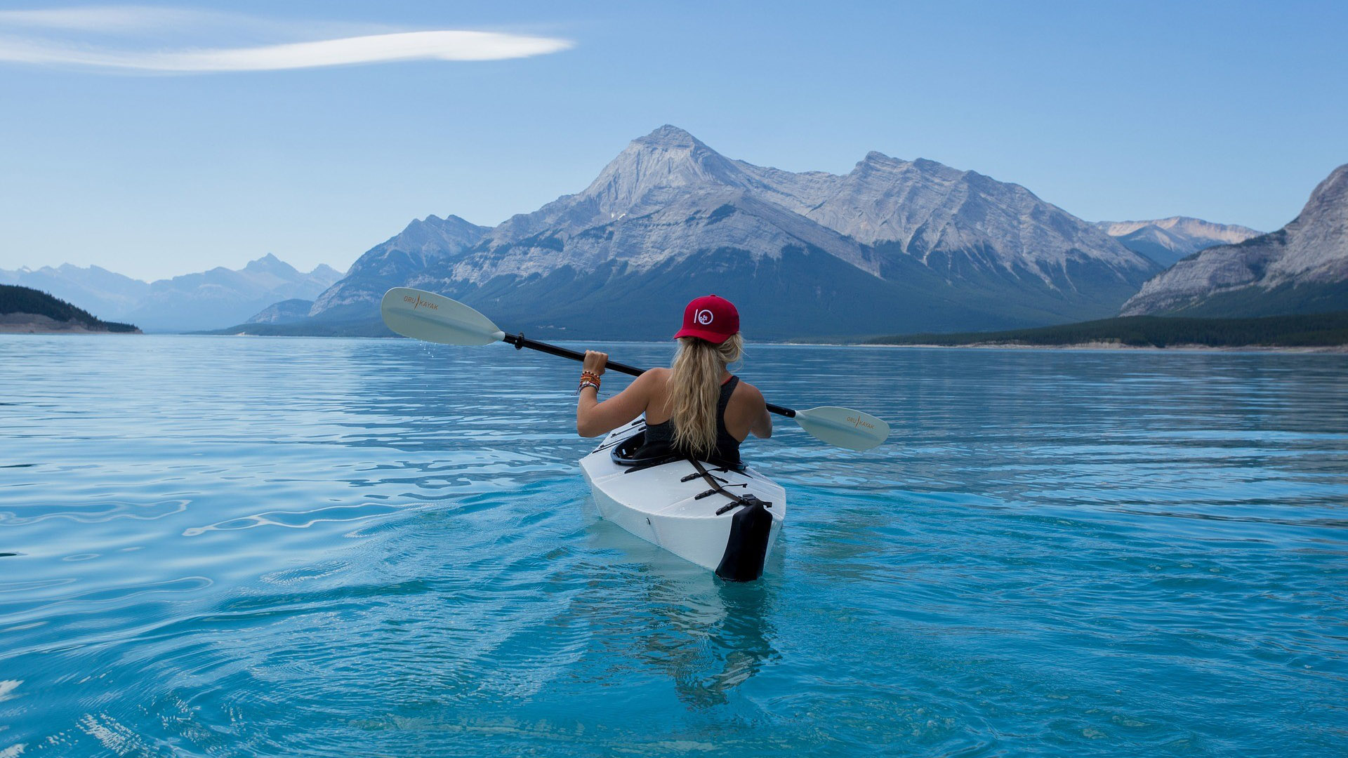 A woman in a kayak in mountain landscape